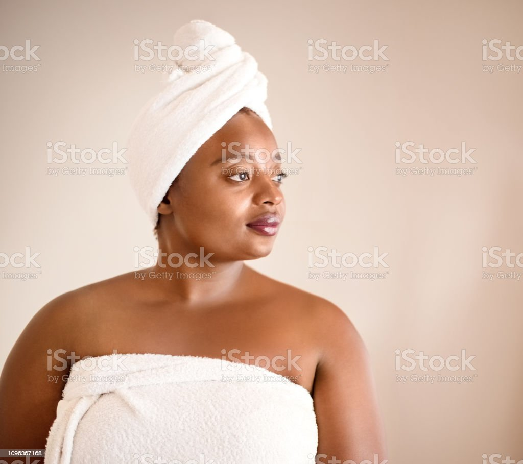 Shot of african woman wrapped in a towel standing against brown...