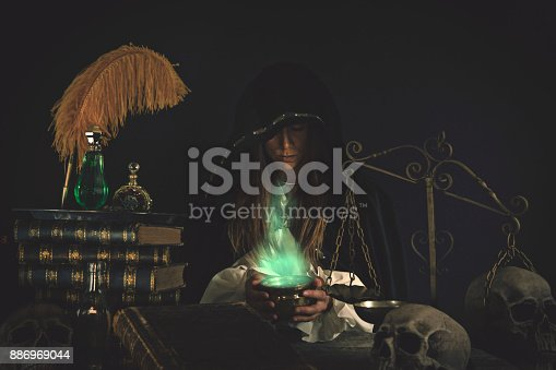 Woman wizard at an old alchemists work table with mystical items, books, potions, skulls, scales and other equipment.