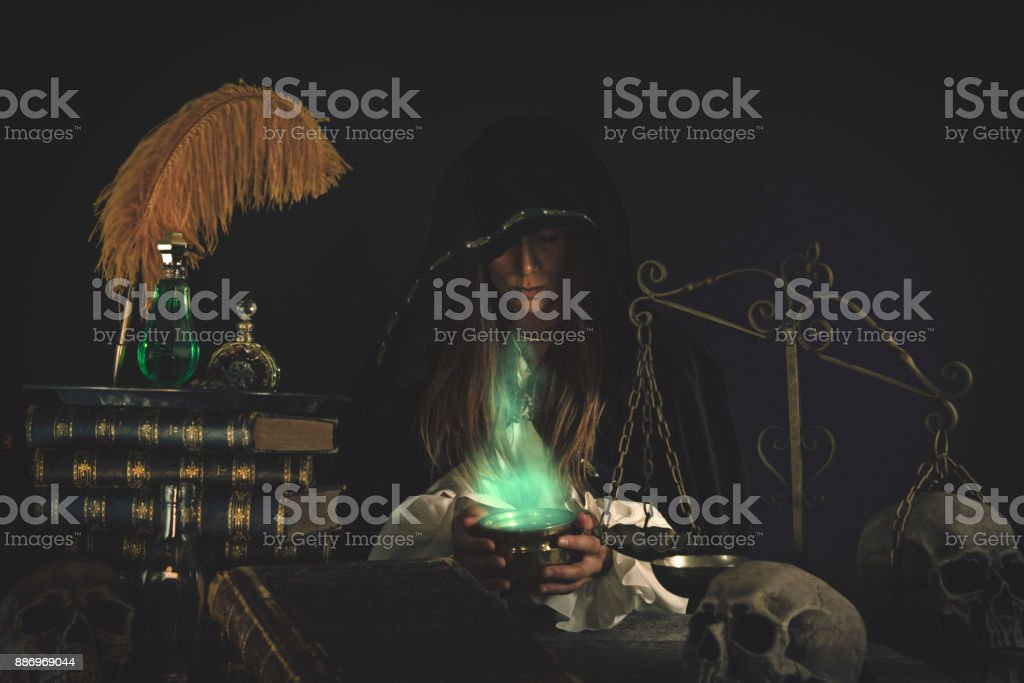 Female Wizard at table with Magical Items stock photo