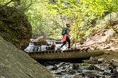 A woman hikes through the mountains of utah along a dirt path. She is crossing a wooden bridge over a small creek.