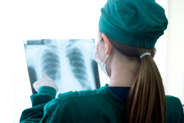 Female women medical doctor looking at x-rays in a hospital Female women medical doctor looking at x-rays in a hospital .checking chest x ray film at ward x ray equipment stock pictures, royalty-free photos & images