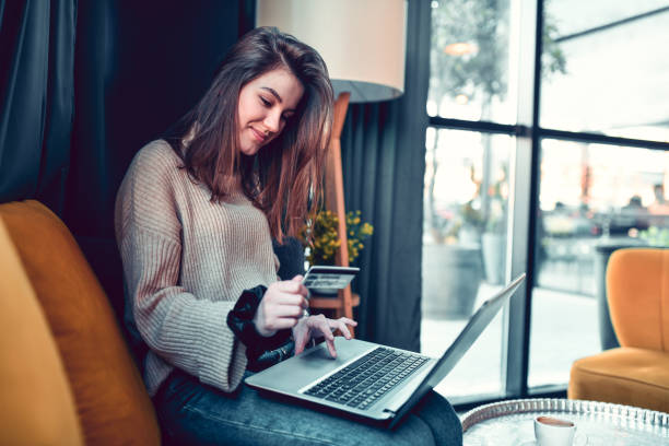 Female Wondering What To Buy Online On Laptop stock photo