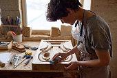 Female wood carver finishing furniture detail