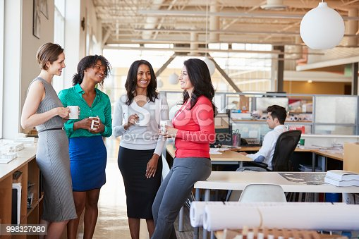 istock Female work colleagues chatting over coffee in the office 998327080
