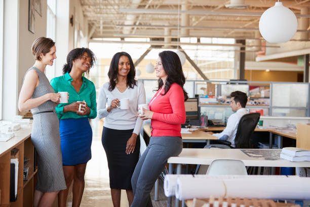 female work colleagues chatting over coffee in the office - friendly work stock photos and pictures
