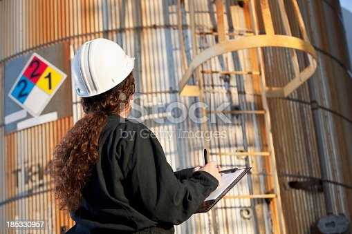 Young woman working at chemical plant, standing in front of storage tanks with clipboard.