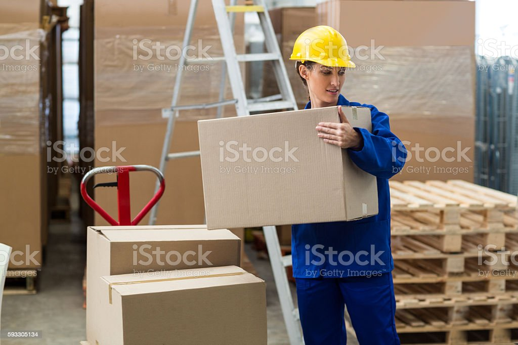 Female worker carrying a box stock photo