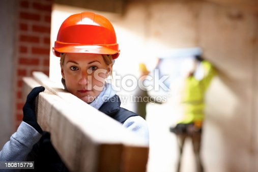 istock Female worker carrying wood at constructions site 180815779