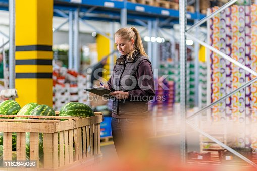 Female worker with clipboard checking shipment of watermelons in warehouse.