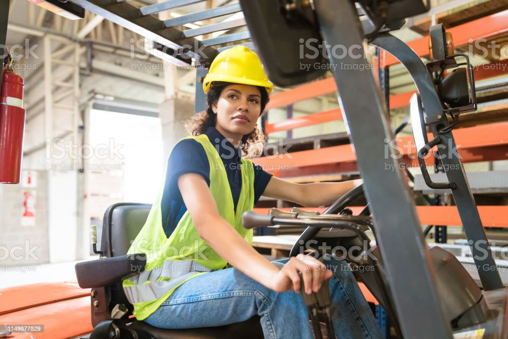 Female worker driving forklift in industry Mid adult female worker driving forklift in industry. Engineer is occupied in manufacturing sector. She is with confident look on her face. 30-34 Years Stock Photo