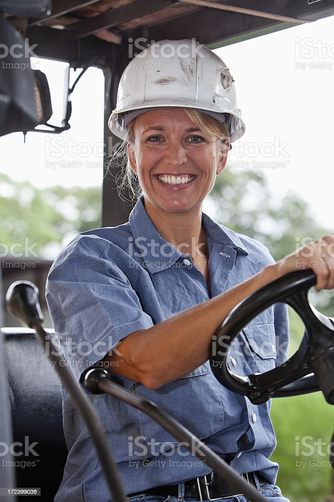 Female worker driving forklift stock photo