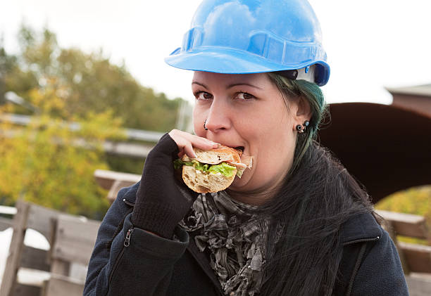 Female worker eating sandwich stock photo