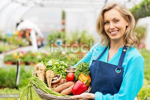 istock Female Worker Holding Basket Of Fresh Vegetables 171296252