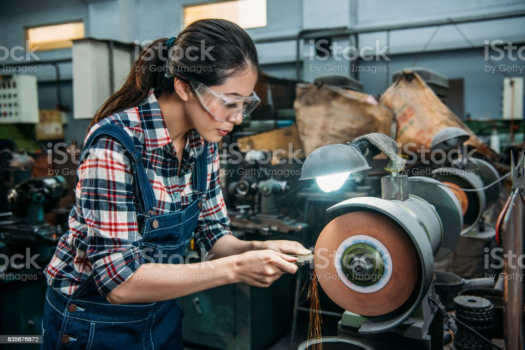 female worker holding components metal grinding ストックフォト