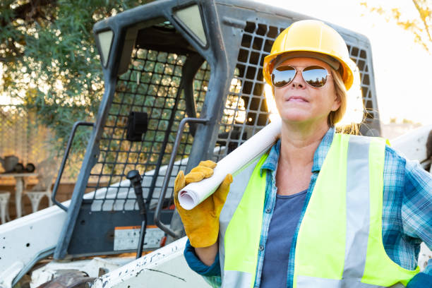 Female Worker Holding Technical Blueprints Near Small Bulldozer At Constrcution Site stock photo