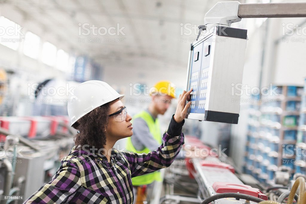 Female worker in factory using control panel for machine stock photo