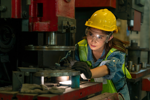 Female worker in hard hat and safety glasses working in the manufacturing industry on business day. Technician engineer control machines in an industrial factory. Workplace gender equality concepts\