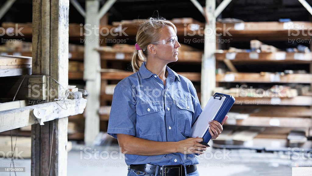 Female worker in lumber store taking inventory stock photo
