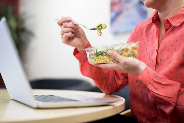 オフィスのデスクで健康パスタ昼食の女性労働者 - 昼食 ストックフォトと画像
