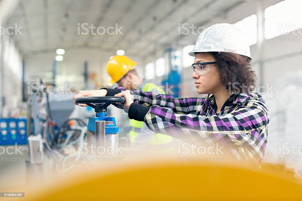 Female worker in the factory working on a machine stock photo