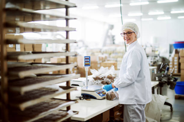 Female worker measuring cookies and putting them into plastic bags while standing and looking at camera. Food factory interior. Female worker measuring cookies and putting them into plastic bags while standing and looking at camera. Food factory interior. hair net stock pictures, royalty-free photos & images