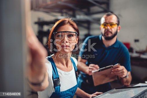 istock Female worker operate machine in factory 1140346326