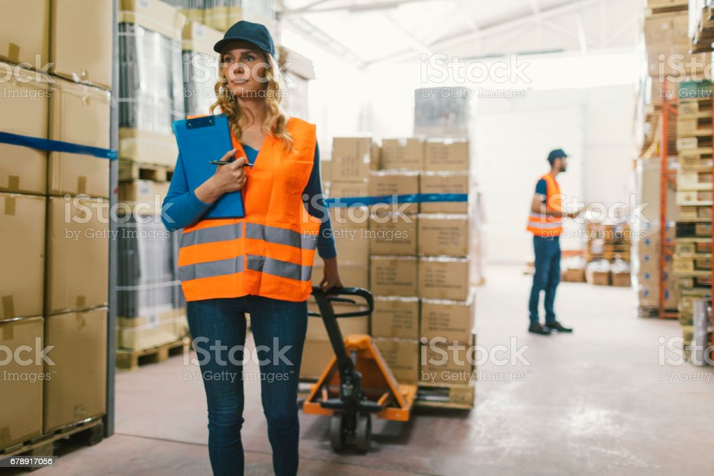 Female worker pulling pallet jack stock photo