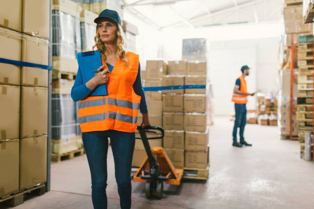 Female worker pulling pallet jack Female worker pulling pallet jack and holding checklist. Her male colleague working  in background pallet jack stock pictures, royalty-free photos & images