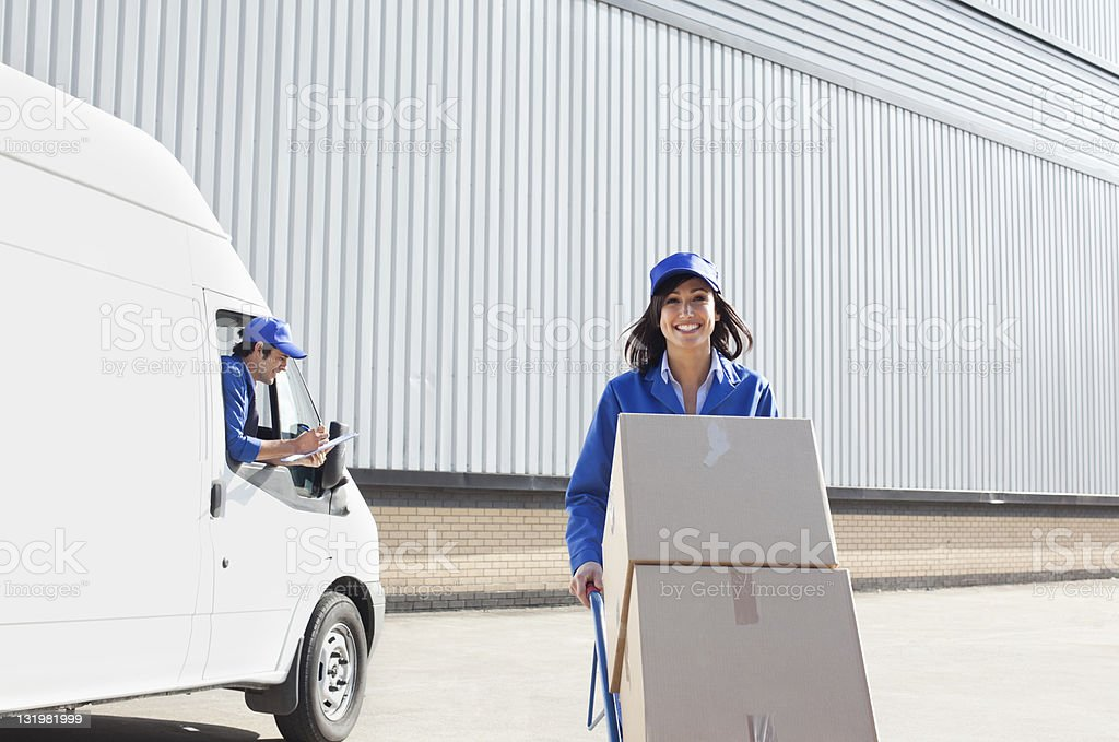 Female worker pushing hand truck while driver seating in van with checklist royalty-free stock photo