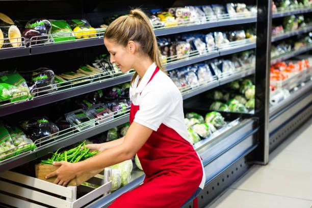 female worker putting vegetable box in shelf - supermarket worker imagens e fotografias de stock