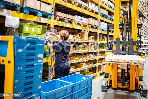 istock Female worker reading codes at warehouse 1097357658