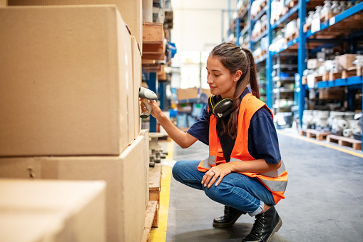 Warehouse worker crouching down and checking boxes on shelves with scanner. Female worker scanning boxes in rack.