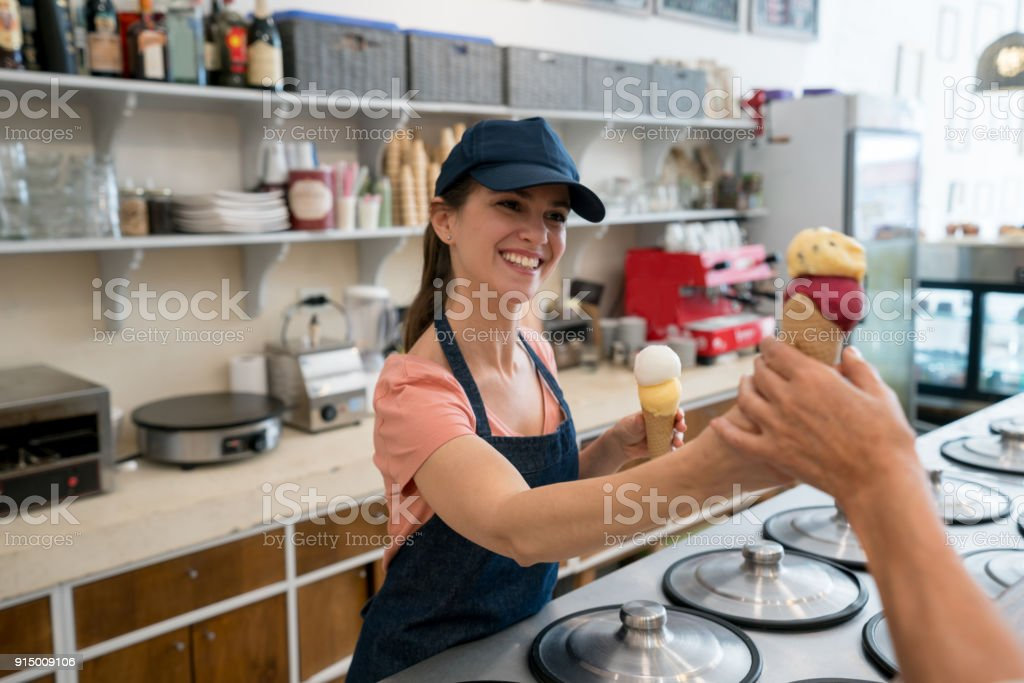 Female worker serving an ice cream to an unrecognizable customer at the ice cream parlor stock photo