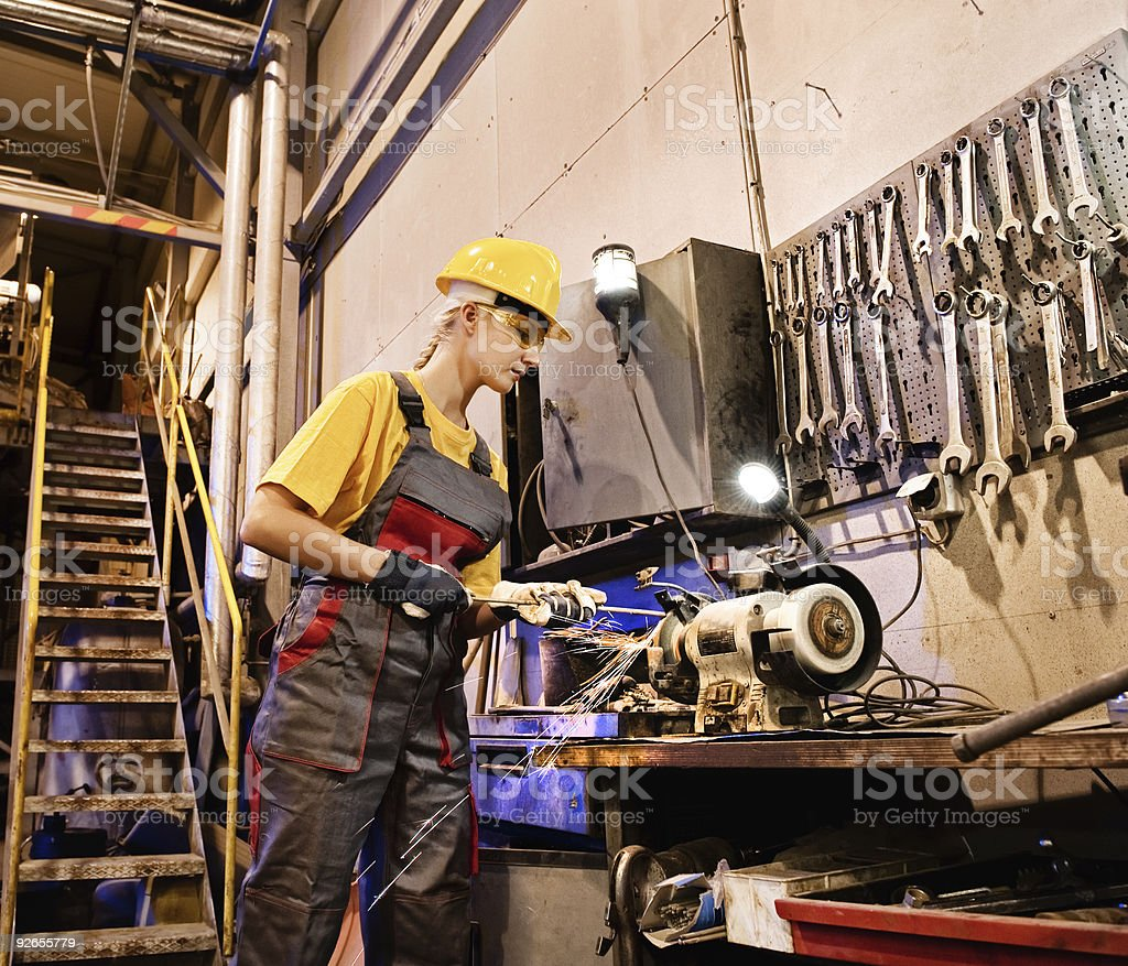 Female worker sharpening tools in a machine shop royalty-free stock photo
