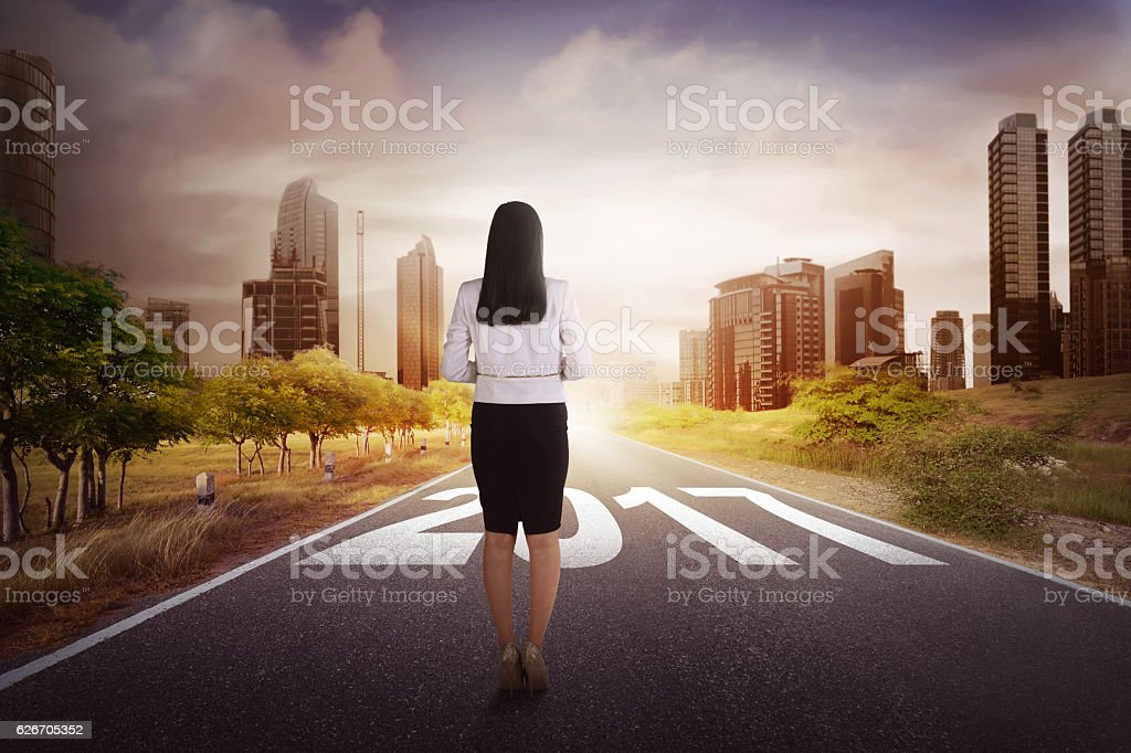 Female worker starts walking her journey on a street to stock photo