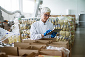 istock Female worker using tablet for checking boxes while standing in food factory. 1072243246