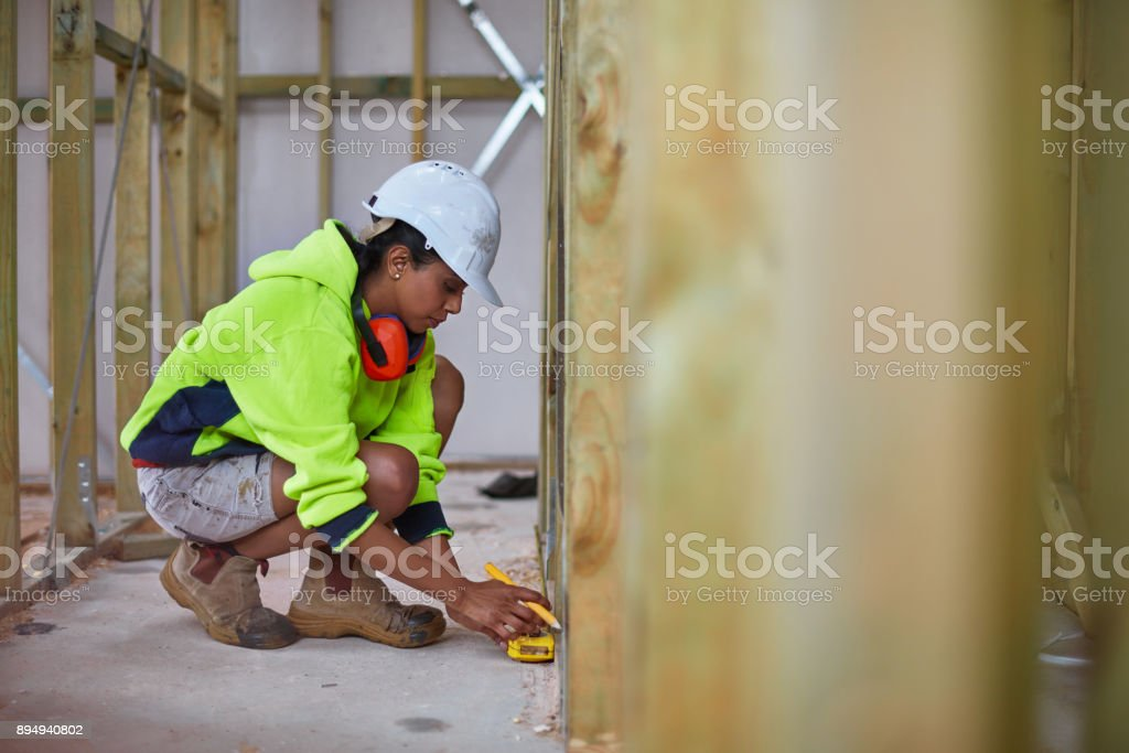 Female worker using tape measure at site stock photo