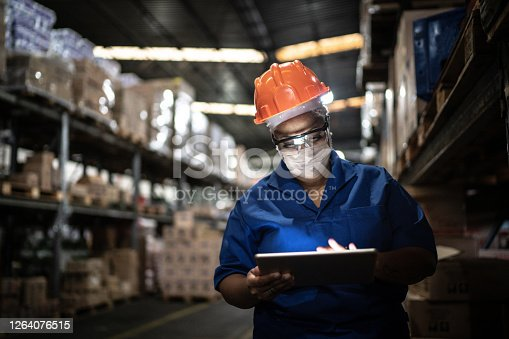 Female worker walking and using digital tablet in warehouse
