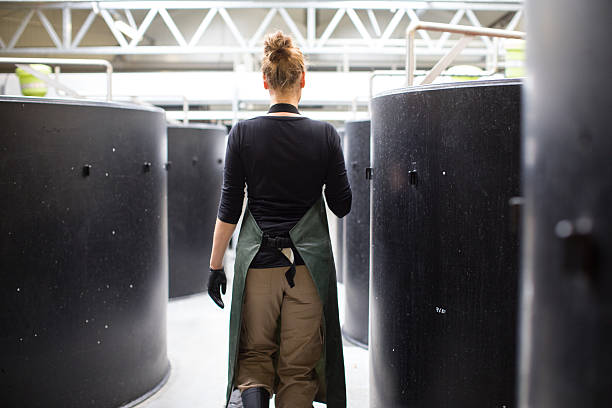 Female worker walking through storage tanks in fish farm stock photo