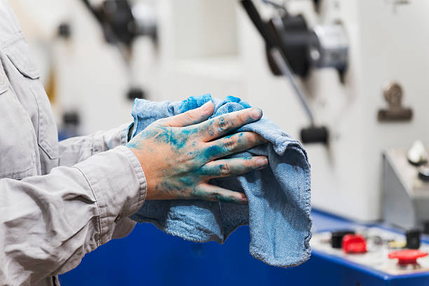 Female worker wiping hands with rag stock photo