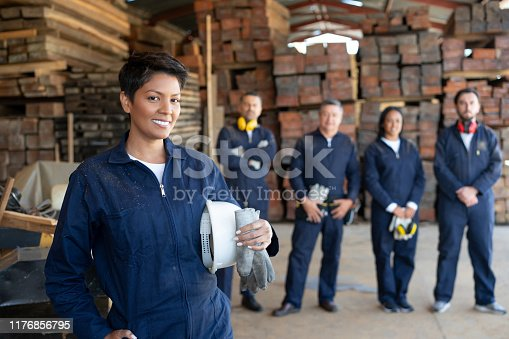 Portrait of a Latin American worker with a group at a wood factory – manufacturing concepts