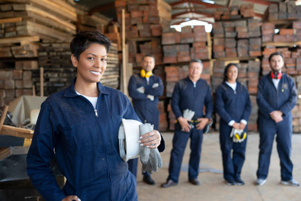 Female worker with a group at a wood factory Portrait of a Latin American worker with a group at a wood factory – manufacturing concepts labor union stock pictures, royalty-free photos & images