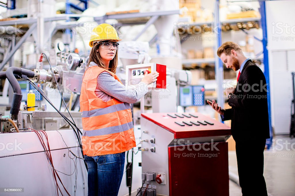 Female worker with quality control inspector in the factory stock photo