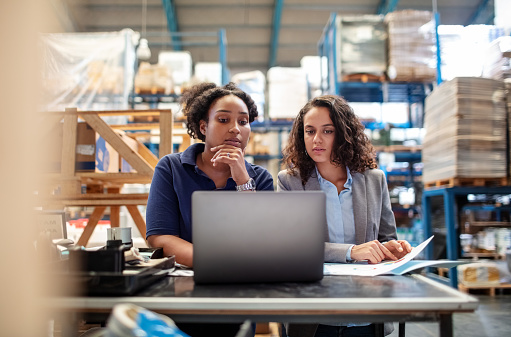 Female worker with supervisor working on laptop. Factory workers working together.