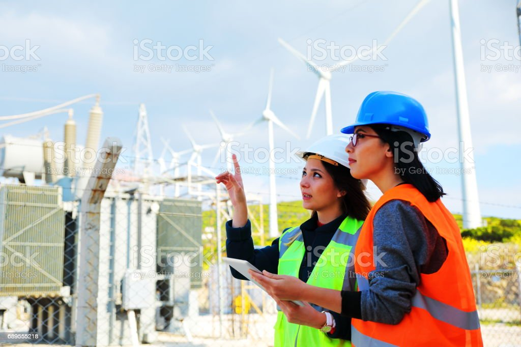 Female workers in a wind turbines farm stock photo