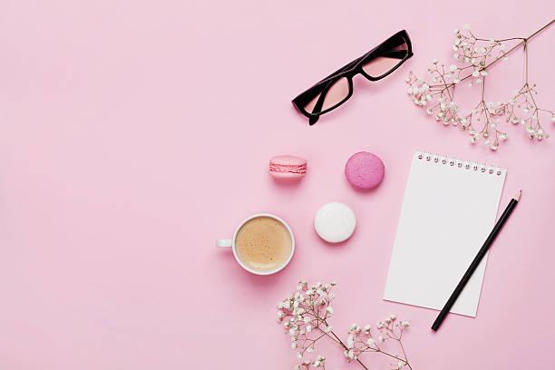 female working desk. coffee, macaroons, notebook, eyeglasses, flowers. flat lay. - modetorten stock-fotos und bilder