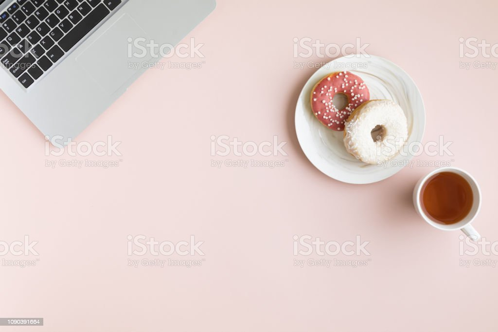 Female working desk with dessert and coffee. Donuts with a cup of...