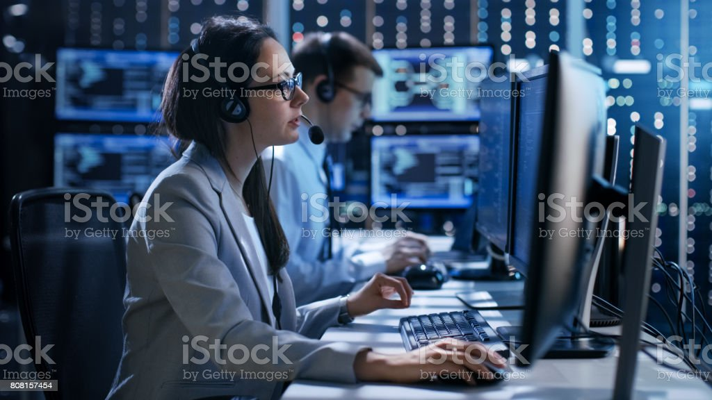 Female working in a Technical Support Team Gives Instructions with the Help of the Headsets. In the Background People Working and Monitors Show Various Information. stock photo