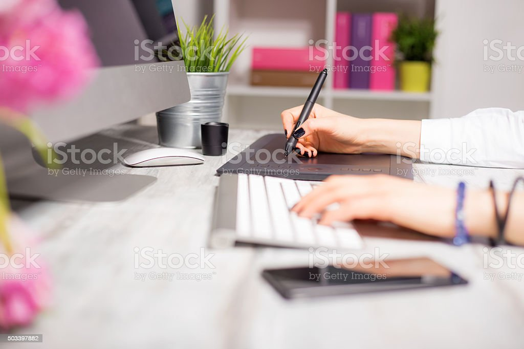 Female working on computer and drawing pad stock photo
