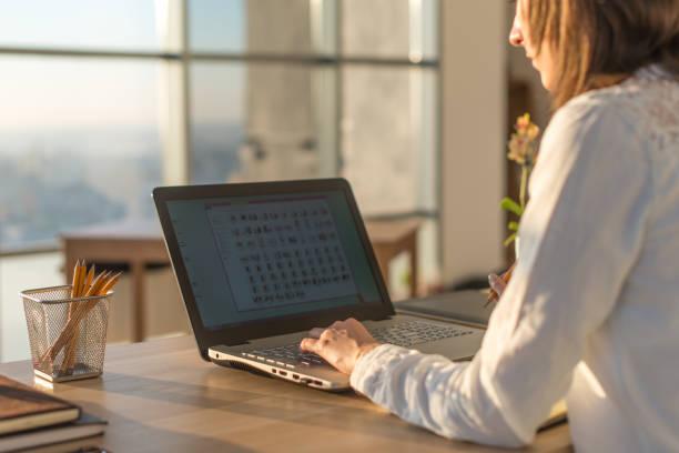 vrouwelijke schrijver typen met behulp van laptop toetsenbord op haar werk in de ochtend. vrouw schrijven blogs online, kant bekijk close-up foto. - e learning stockfoto's en -beelden